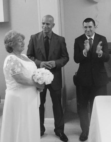 El novio y el padrino miran con amor a la novia
