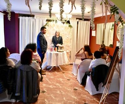 El novio, los invitados y la oficiante de bodas esperando la entrada del cortejo